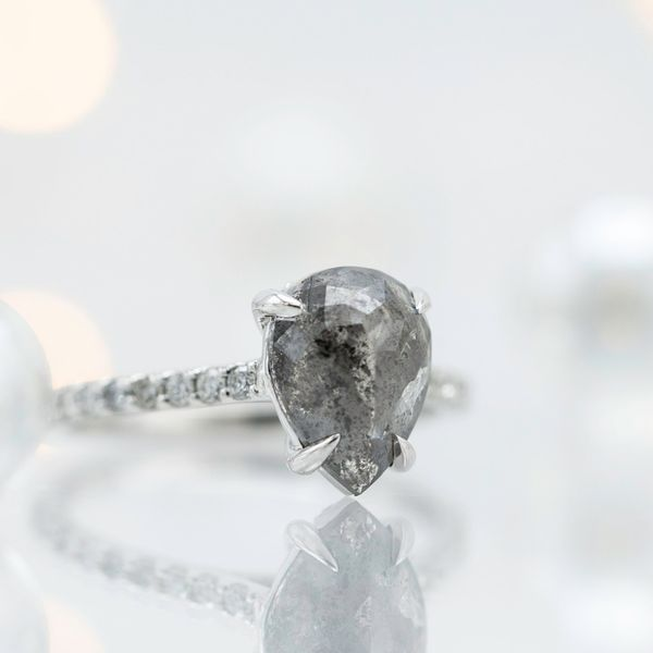 A gorgeous pear cut salt and pepper diamond steals the show in this modern pave engagement ring.