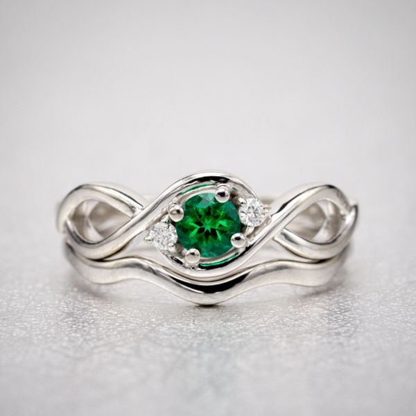 Organic, nature-inspired curves in this bridal set. Small diamond accents seem to orbit the round emerald, reinforcing the twist of the white gold shank.