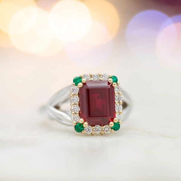 Emeralds and diamonds combine to create a distinctive halo for this emerald cut ruby ring.