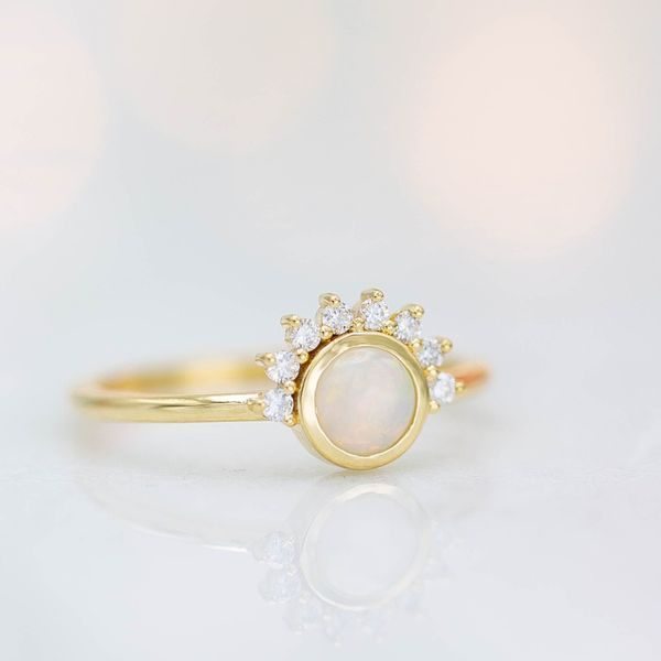 A sunburst-styled half halo surrounds the bezel set oval in this engagement ring.