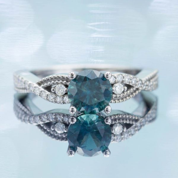 This ring's vining shank surrounds the teal blue-green sapphire center stone.