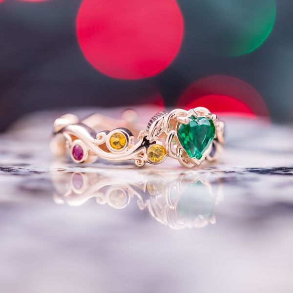 "He told us ""she is the one who brought color into my life."" So we designed a nature-inspired ring with a rainbow of colored accent gems around the emerald center stone."
