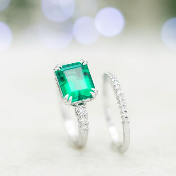 Emerald engagement ring and matching wedding band, with east-west setting for the emerald cut center stone.