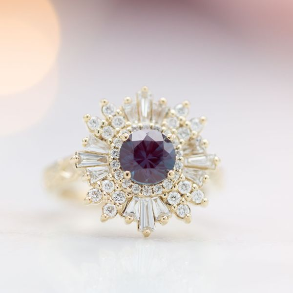A bold combination of baguette and round halo stones create a ballerina halo around this alexandrite center stone.