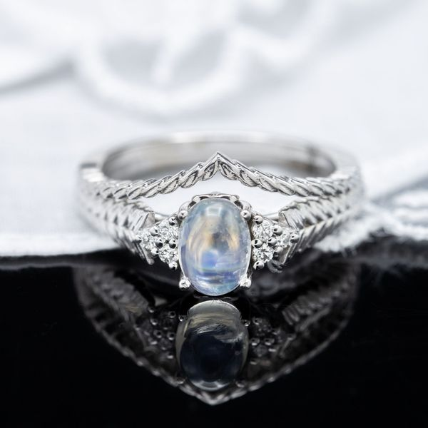This bridal set surrounds a moonstone with a bit of diamond sparkle and a distinctive wheat texture detailing the band.