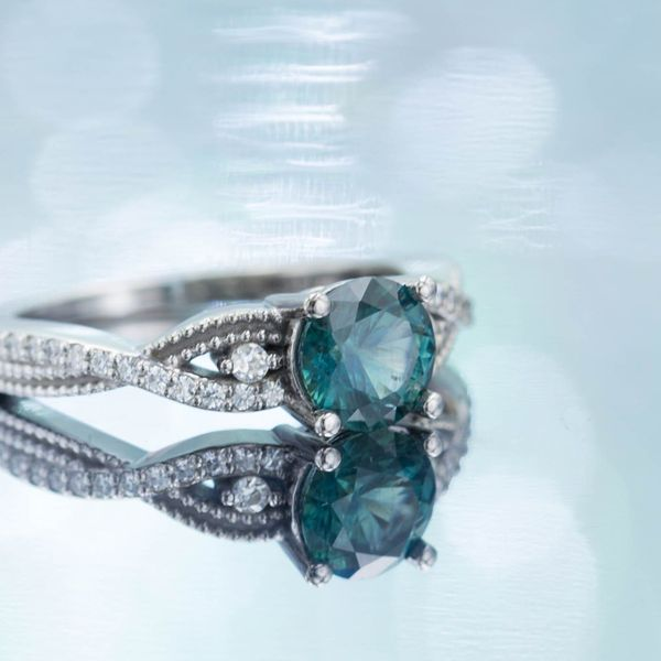 This teal-blue sapphire engagement ring has a twisting band and diamond accents.