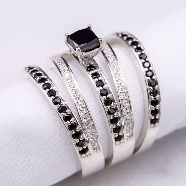 A bold but light design winds multiple strands of white gold around the finger. Mixing white and black diamonds and a square cut center stone with curving lines gives this piece beautiful contrast.