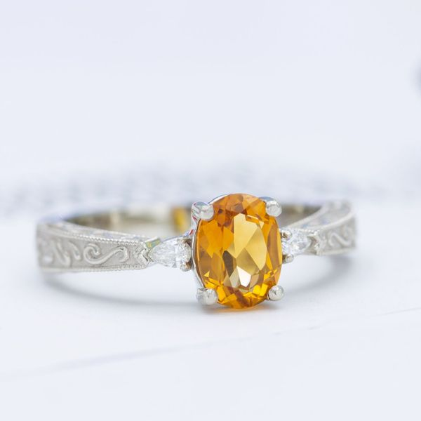 Three stone engagement ring with citrine and diamonds with scrollwork and milgrain on the band.