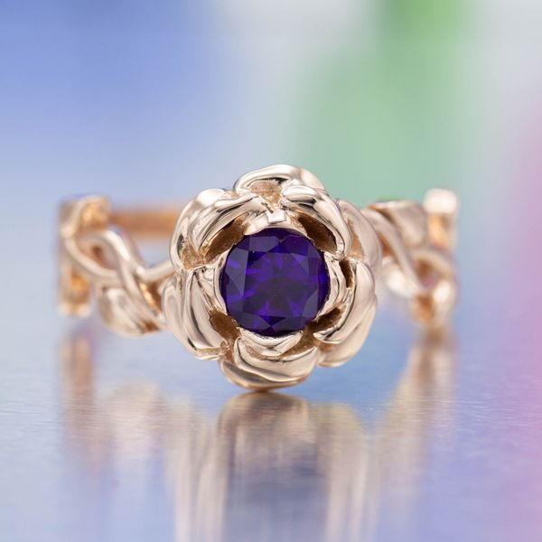 A pop of deep purple amethyst gives this rose gold rose ring a wonderfully unusual color.
