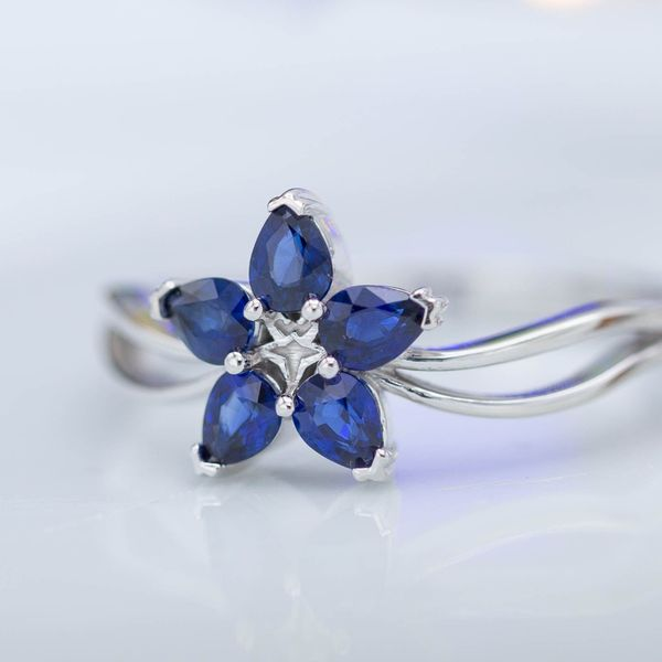 Five deep blue sapphire petals on a dainty white gold band to form a bright, whimsical flower ring.