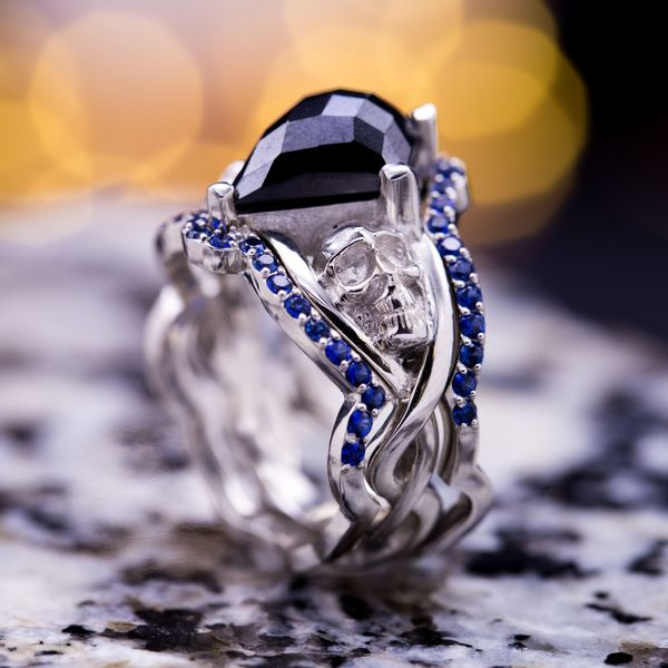 A bold bridal set with an unusual checkerboard kite-cut black diamond and sapphire-lined enhancer bands.