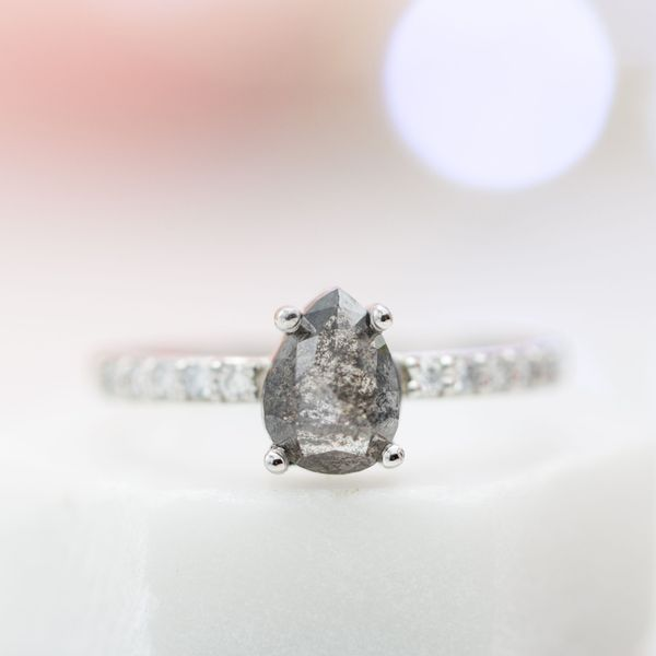 A classic pave solitaire ring with an unforgettable center stone: a galaxy of inclusions scattered throughout the body of this rose cut pear diamond.