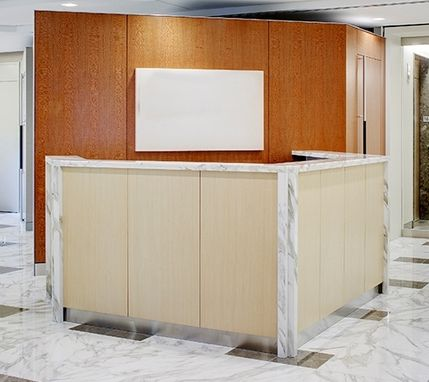 Custom Made Angled Reception Desk With Stone Top And Wood Panel Insets