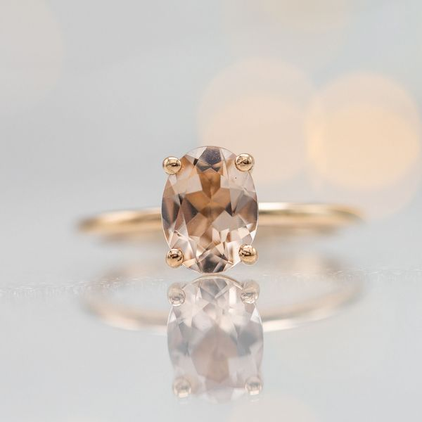 This oval cut morganite has a peachy-pink color and pairs perfectly with a delicate rose gold band.