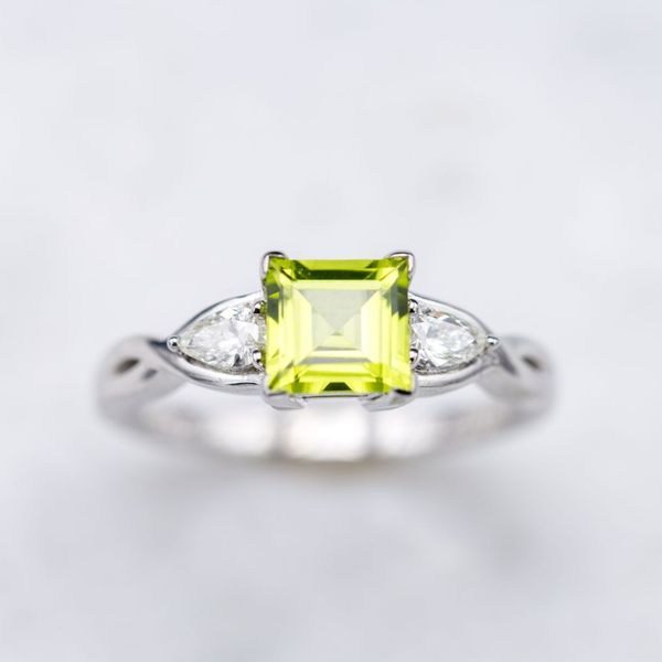 A step cut square peridot surrounded by pear cut diamonds in a modern engagement ring.