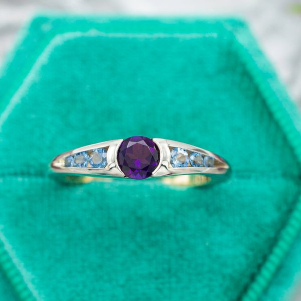 The amethyst center stone in this ring has a semi-bezel setting, with openings on two sides that show off more of the gem.
