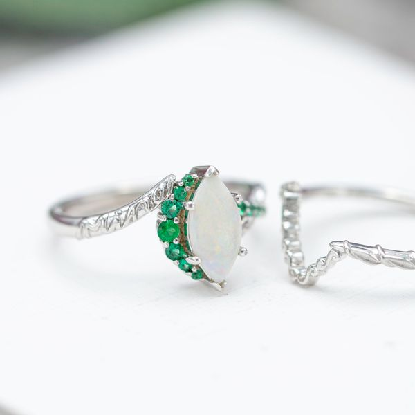 This unique engagement ring uses graduated emeralds to create a crescent moon semi-halo along the length of the marquise opal.
