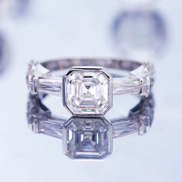 The stark geometry of an asscher cut center stone and tapered baguette side stones gives way to beautifully ornate curves halfway down the band.