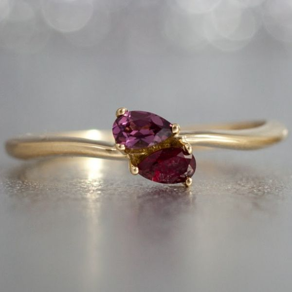 A sweet toi-et-moi ring nestles a pear rhodolite garnet next to a ruby in a delicate, wavey yellow gold ring.