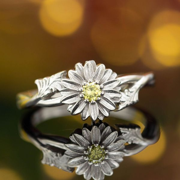 A perfectly delicate daisy ring with a fancy yellow diamond at its heart.