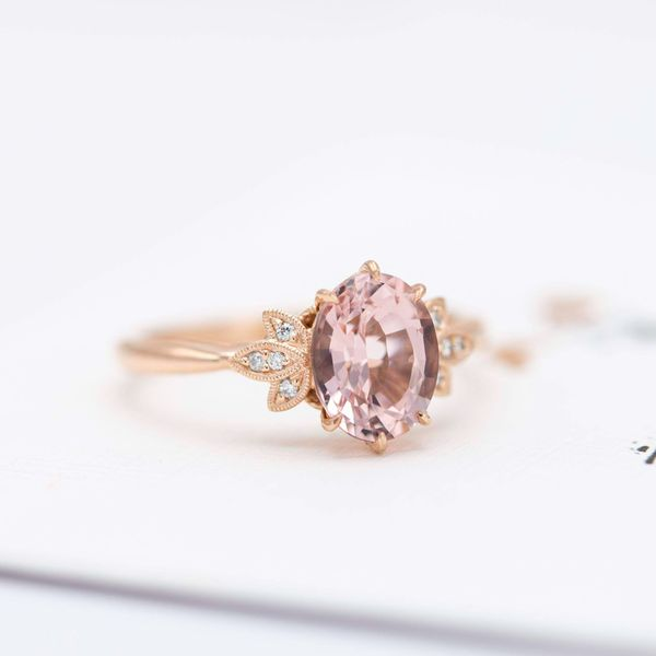 The finished morganite engagement ring created from the sketches above, with a bright burst of diamonds around the oval center stone.