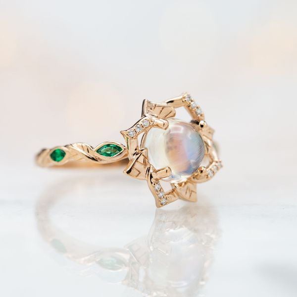 Open petal lines frame a moonstone center stone, giving this bold ring an extremely delicate and feminine appearance.