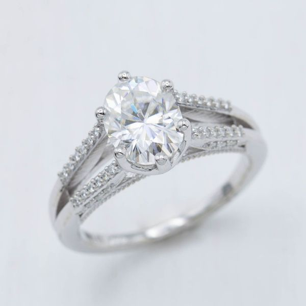 A modern split shank setting with an oval center stone spanning the gap between the pave white gold bands.
