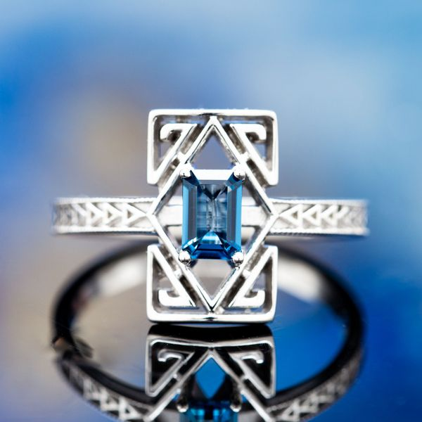 The Deco geometry of repeating triangles on the band and angular spiraling lines (reminiscent of a Greek Key motif) surround a London Blue Topaz center stone.