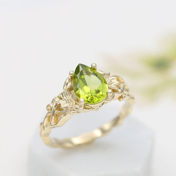Sculptural, floral ring inspired by a dogwood branch and flowers, with a pear cut peridot center.
