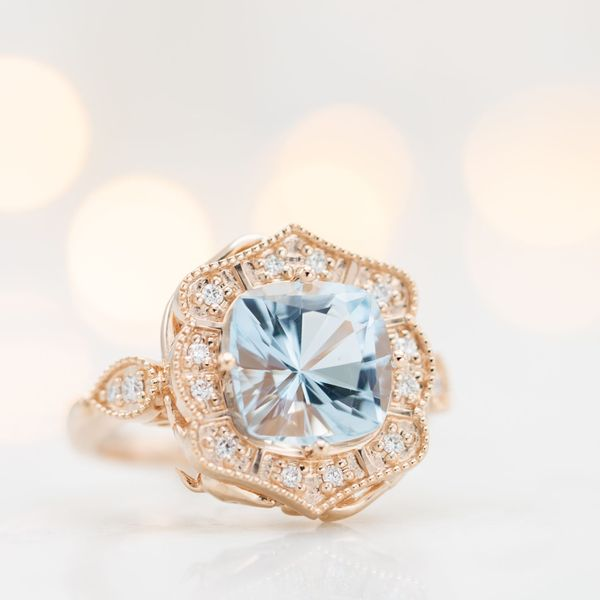 Rose gold engagement ring with an antique frame halo around a brilliant cushion cut aquamarine.