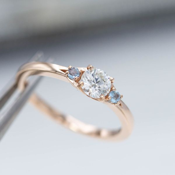 Three-stone setting for a half-carat diamond and accent aquamarines in rose gold.