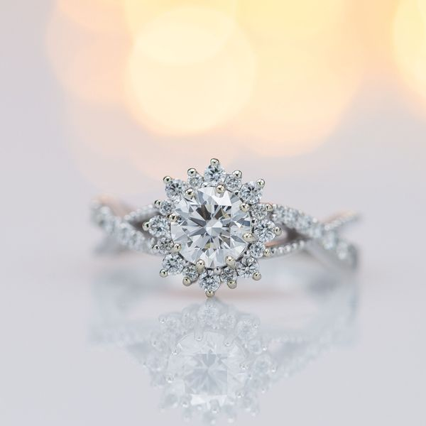 We chose diamonds in this ring's sunburst halo at the same color grade as the center stone, to avoid highlighting any tint in the center stone.