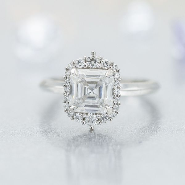 The stark geometry of this asscher cut center stone is softened by the curves of the surrounding halo.