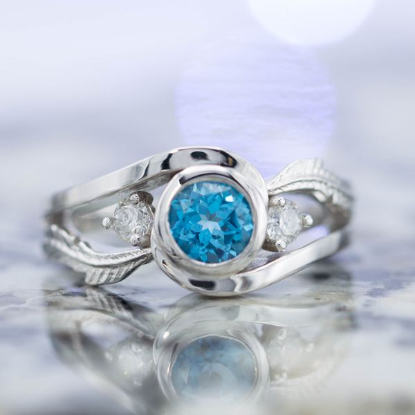 Inspired by the game Harvest Moon, in which a blue feather is given as symbol of a marriage proposal. Our design features delicate white gold feathers and a Swiss blue topaz to bring in the blue.