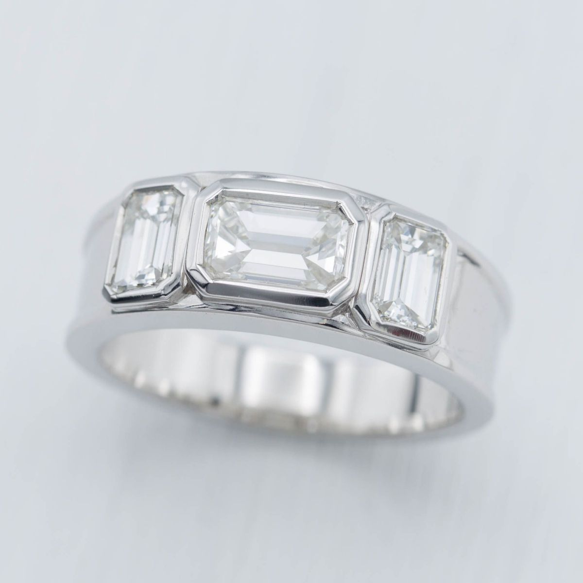 65791718c A minimal, chunky band style engagement ring. Octagonal bezel settings for  the emerald cut diamonds to reinforce the shapes.