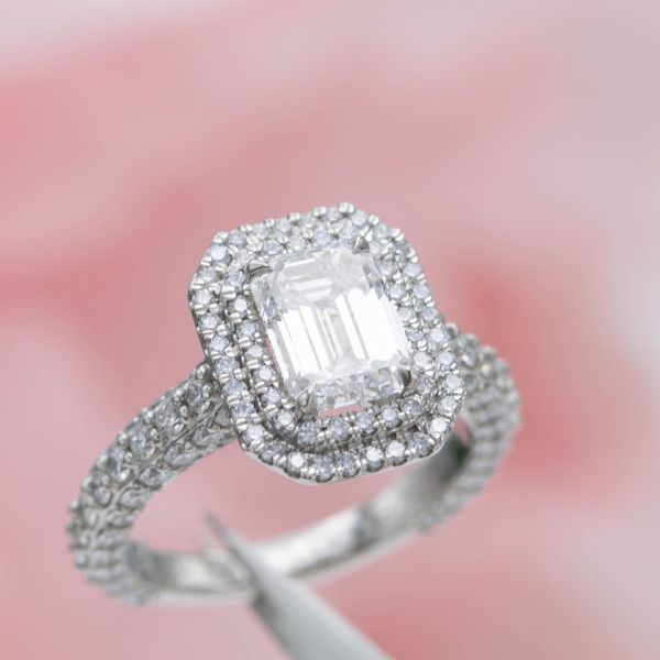 An emerald cut diamond engagement ring with a double halo and pave on every side of the band.