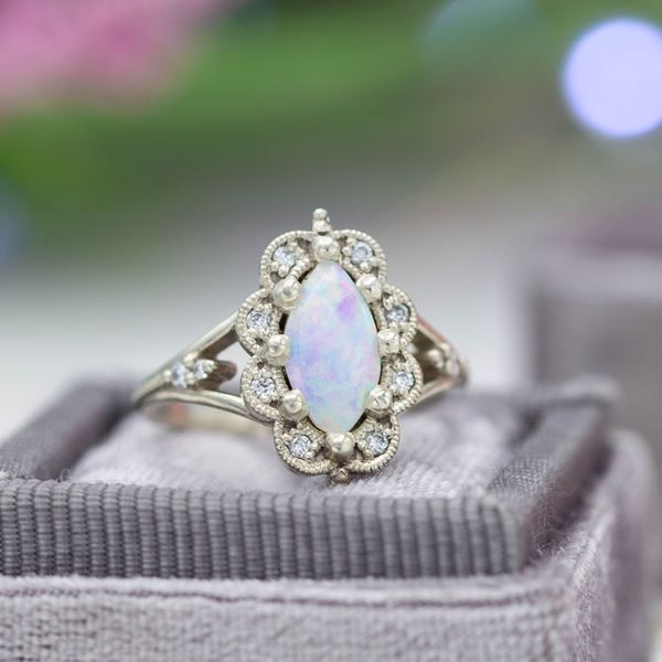 A vintage-inspired marquise cut opal engagement ring with an exaggerated scalloped frame halo.