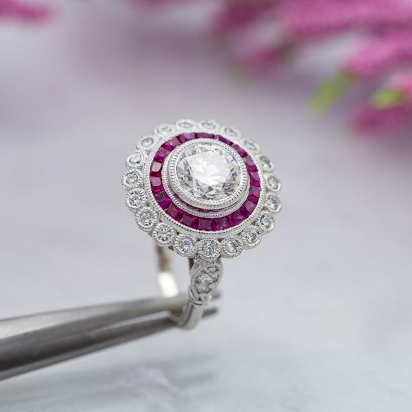 A classic Art Deco-inspired halo ring with calibré-cut rubies forming a perfect inner halo.