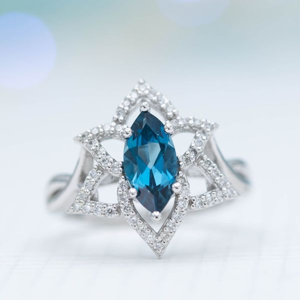 Open, halo-style engagement ring with London blue topaz, inspired by the amaryllis flower.