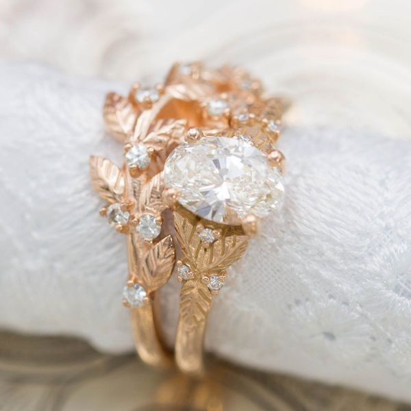 A beautiful nature-inspired bridal set in rose gold, surrounding an 0.72ct oval diamond with delicate leaves.