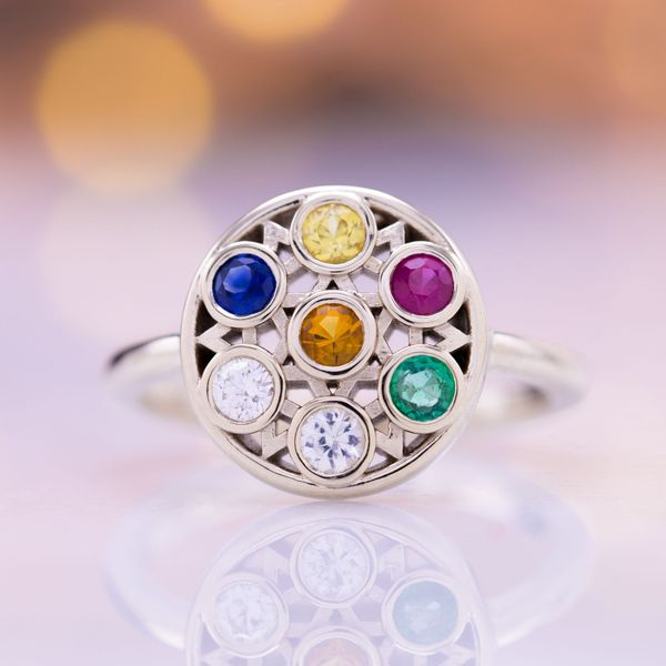 A bright rainbow of colors bezel set with a star pattern in white gold framing the gems.
