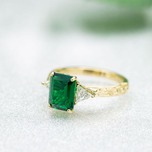 Delicate 3-stone emerald engagement ring with triangle diamond side stones and a leaf-detailed, tapered band.