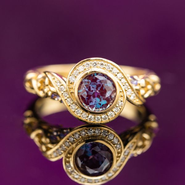 Yellow gold bypass ring with diamond halo around the alexandrite center stone.