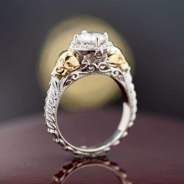 A classic vintage-inspired white gold and diamond ring with a floral halo and yellow gold skull accents.