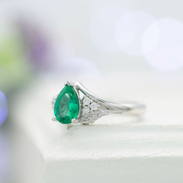 Emerald engagement ring with accent diamonds and peacock feathers.