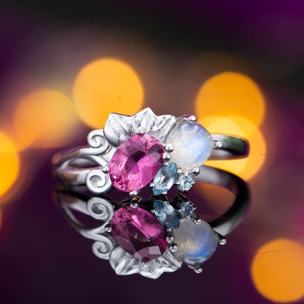 A modern, asymmetric cluster ring combines moonstone, pink tourmaline, and aquamarine in a floral setting.