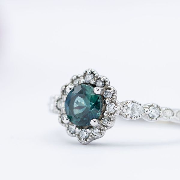 A dusky blue-green sapphire center stone set in a vintage-inspired white gold engagement ring.