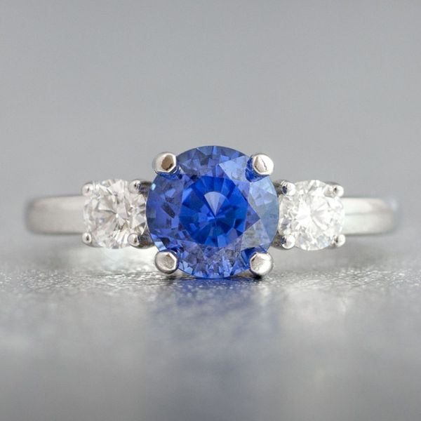 A natural, unheated sapphire is the eye-catching center stone for this white gold three-stone setting, flanked by two brilliant round diamonds.