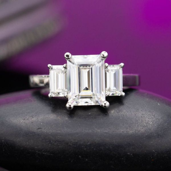 Sleek, geometric 3-stone engagement ring with emerald cut moissanites on a simple platinum band.