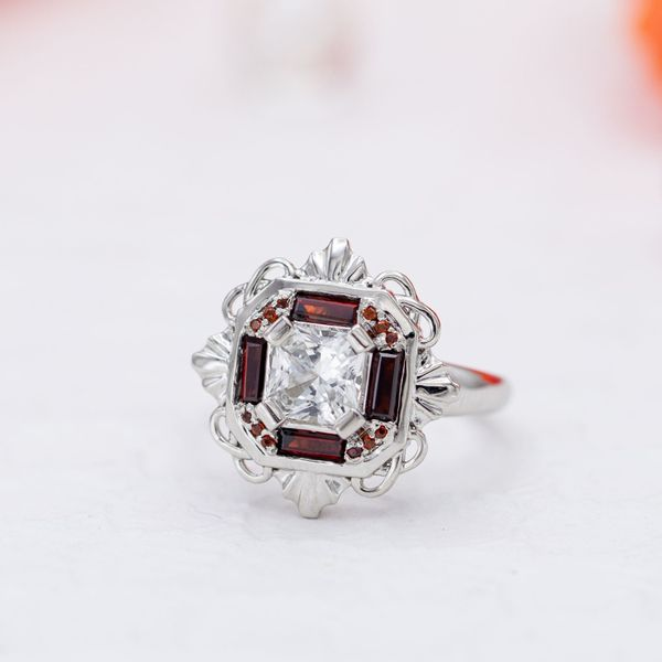 We designed this Art Deco-influenced engagement ring with an asscher cut white sapphire and red garnet accents.